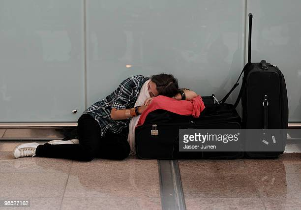 A stranded airline passengers rests her head on her suitcase as she waits at El Prat international airport on April 18 2010 in Barcelona Spain All...