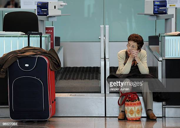 A stranded airline passengers sits on an airline luggage check in belt at El Prat international airport on April 18 2010 in Barcelona Spain All...