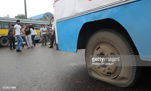 Stranded commuters look on as the tyres of a bus they were travelling in are seen deflated by Bharatiya Janata Party activists at a road block during...