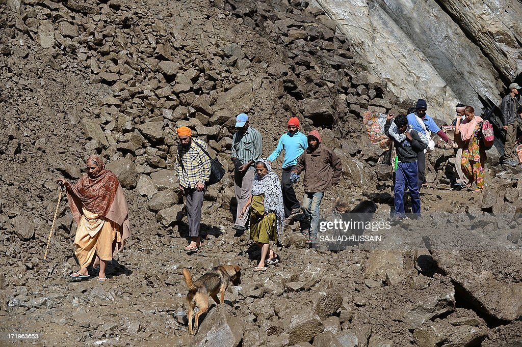 Stranded Hindu pilgrims and villagers make their way across a landslide caused by overnight rains as they make their way down the mountain in Govindghat following flash floods in northern Uttarakhand state on June 30, 2013. Some 3,000 tourists and pilgrims remain missing in India's flood-ravaged north two weeks after the tragedy, but it is unclear how many of those have been killed, a top state official said June 30.