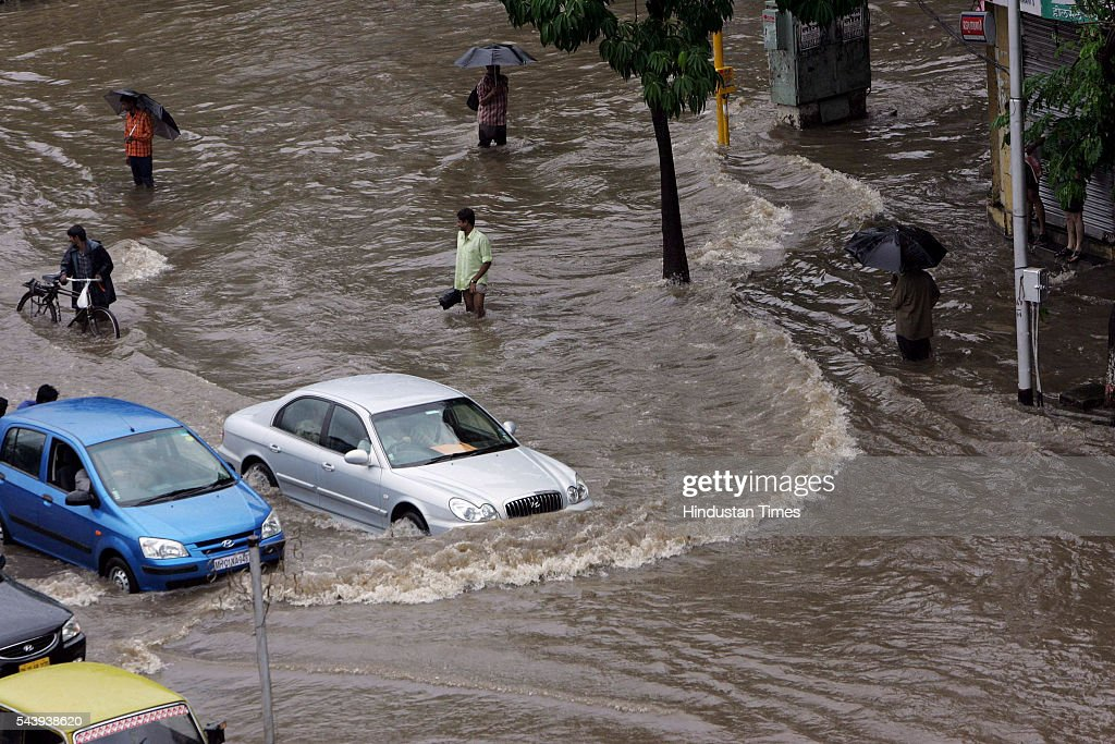 Stranded in the middle of a flooded street near Hindmata Cinema at Parel cars and people wade through knee deep water at Hindmata Cinema on July 21, 2005 in Mumbai, India. Heavy rains lashed across the city flooding most of the city's areas.