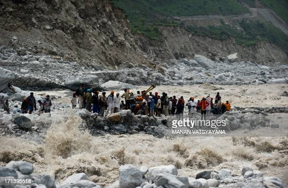 Stranded Indian pilgrims wait to be rescued on the side of a river at Govind Ghat on June 23 2013 Rescue operations have intensified in northern...
