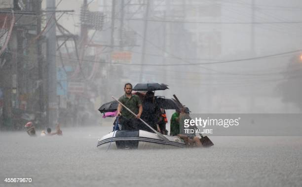 Stranded passengers are ferried through a flooded street during heavy rains brought on by tropical storm FungWong in Manila on September 19 2014...