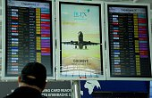 A stranded passengers checks the screens at the departure lounge of Larnaca airport which was closed down following the hijacking of an Egypt Air...