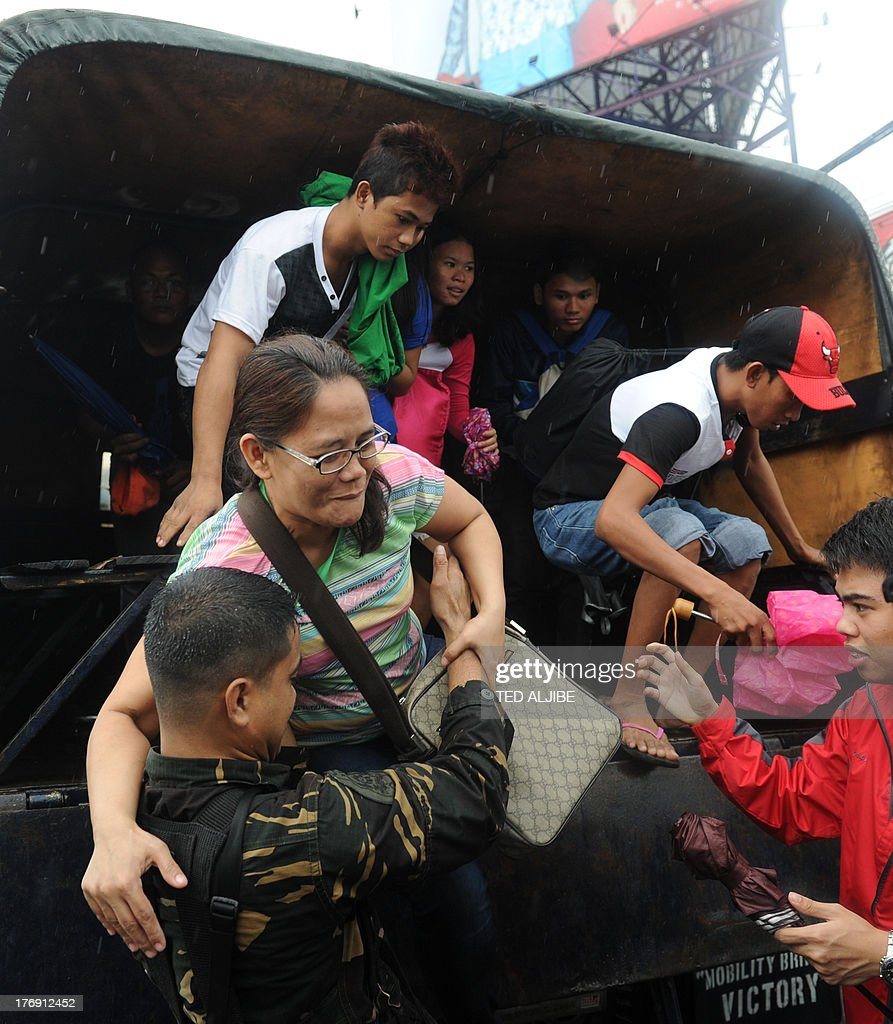 Stranded passengers disembark from a military vehicle which ferried them from flooded streets in Manila on August 19, 2013. Torrential rain paralysed large parts of the Philippine capital August 19, as neck-deep water swept through homes, while floods in northern farming areas claimed at least one life.