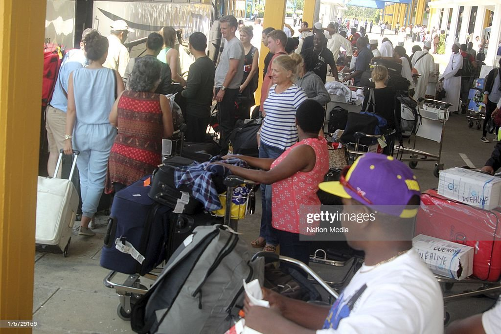 (Not for sale to The Star (Kenya), Capital FM, The People, Citizen TV, Kenya Broadcasting Corporation) Stranded passengers disembark on August 07, 2013 in Nairobi, Kenya. Passengers were unable to leave after JKIA was closed indefinitely after fire gutted part of the international arrivals lobby.