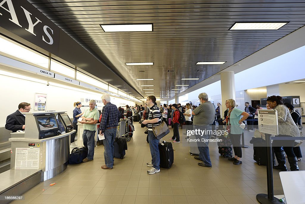 Stranded passengers line up to check in at the US Airways gate as normal operations slowly return after a shooting incident at Los Angeles International Airport (LAX) November 1, 2013 in Los Angeles, California. A man identified as Paul Ciancia reportedly pulled out an assault rifle in Terminal 3 of the airport and shot his way through security, killing one Transportation Security Administration (TSA) worker and wounding several others before being shot himself.