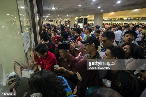 Stranded passengers queue at the airport ticket counter after flight cancellations at Juanda airport near Surabaya located in eastern Java island on...