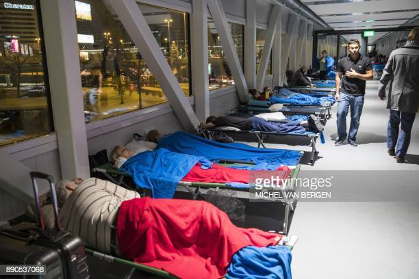 Stranded passengers spend the night on camp beds because their flights have been cancelled at Schiphol Airport The Netherlands on December 11 2017...