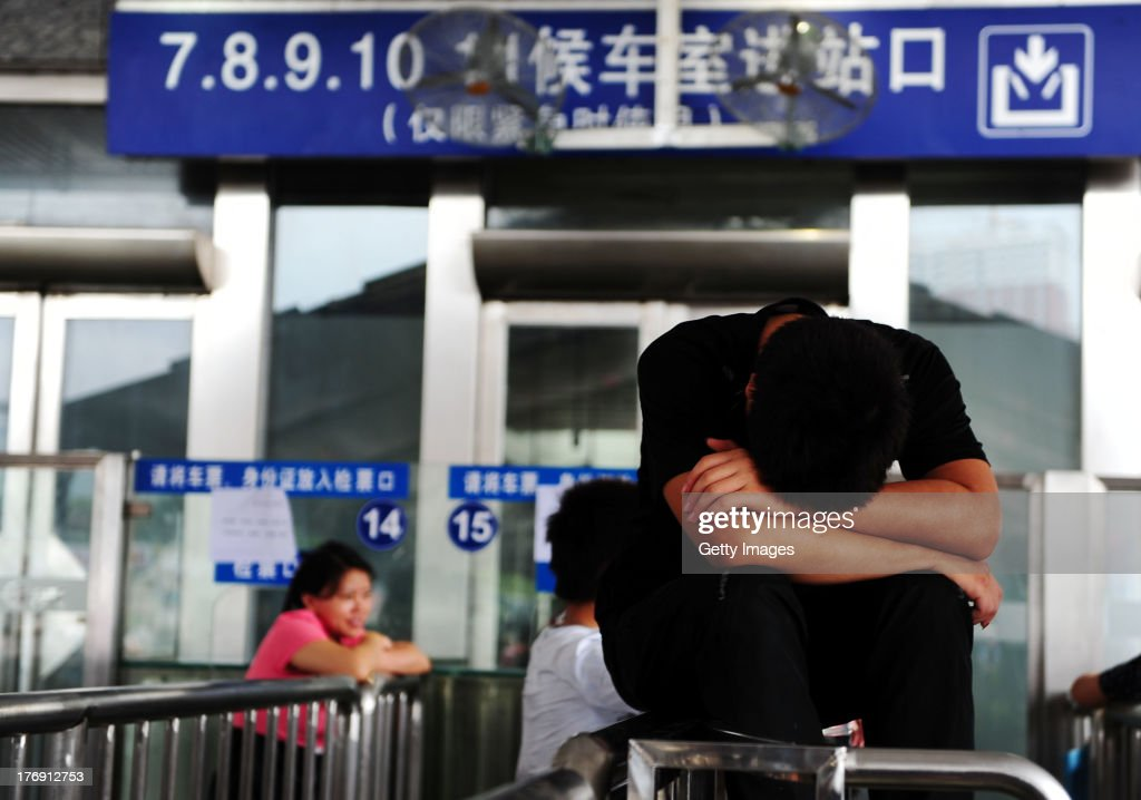 Stranded passengers wait outside the Guangzhou Railway Station on August 18, 2013 in Guangzhou, China. Thousands of passengers have been left stranded at Guangzhou Railway Station, after the railway linking Guangzhou and Beijing was blocked by flood-triggered landslides. Guangdong province has suffered severe rainstorms and flooding after Typhoon Utor hit the area on Wednesday, causing the deaths of 20 people.
