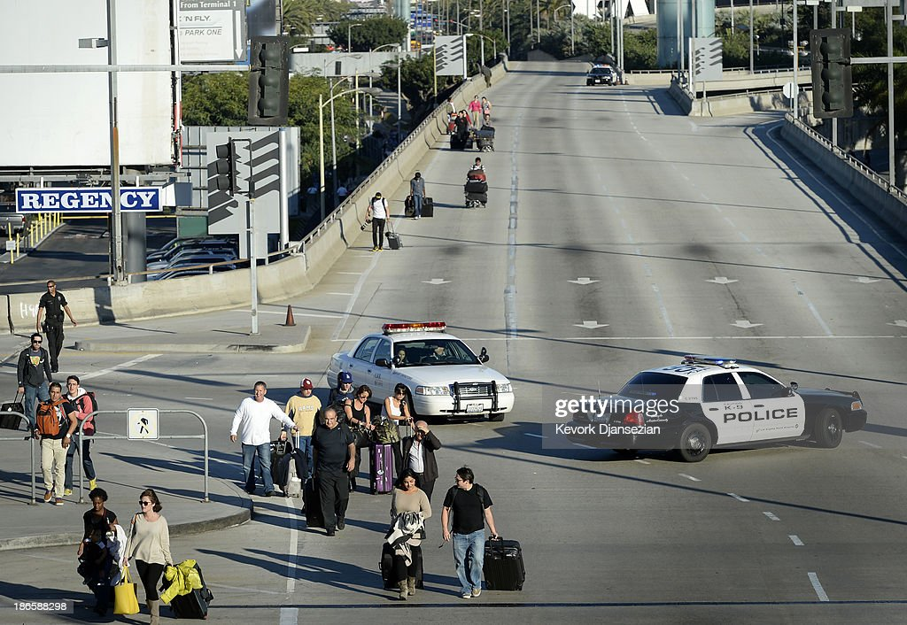 Stranded passengers walk on the closed upper roadway towards the departure gates as normal operations slowly return after a shooting incident at Los Angeles International Airport (LAX) November 1, 2013 in Los Angeles, California. A man identified as Paul Ciancia reportedly pulled out an assault rifle in Terminal 3 of the airport and shot his way through security, killing one Transportation Security Administration (TSA) worker and wounding several others before being shot himself.