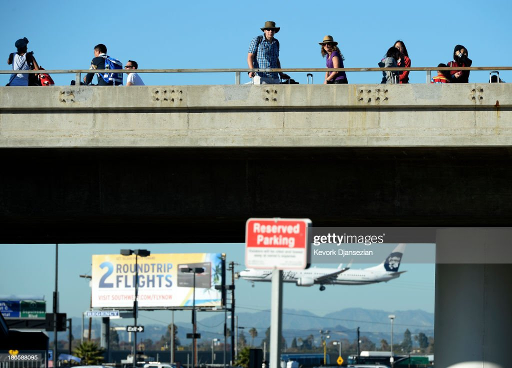 Stranded passengers walk on the upper roadway towards the departure gates as normal operations slowly return after a shooting incident at Los Angeles International Airport (LAX) November 1, 2013 in Los Angeles, California. A man identified as Paul Ciancia reportedly pulled out an assault rifle in Terminal 3 of the airport and shot his way through security, killing one Transportation Security Administration (TSA) worker and wounding several others before being shot himself.