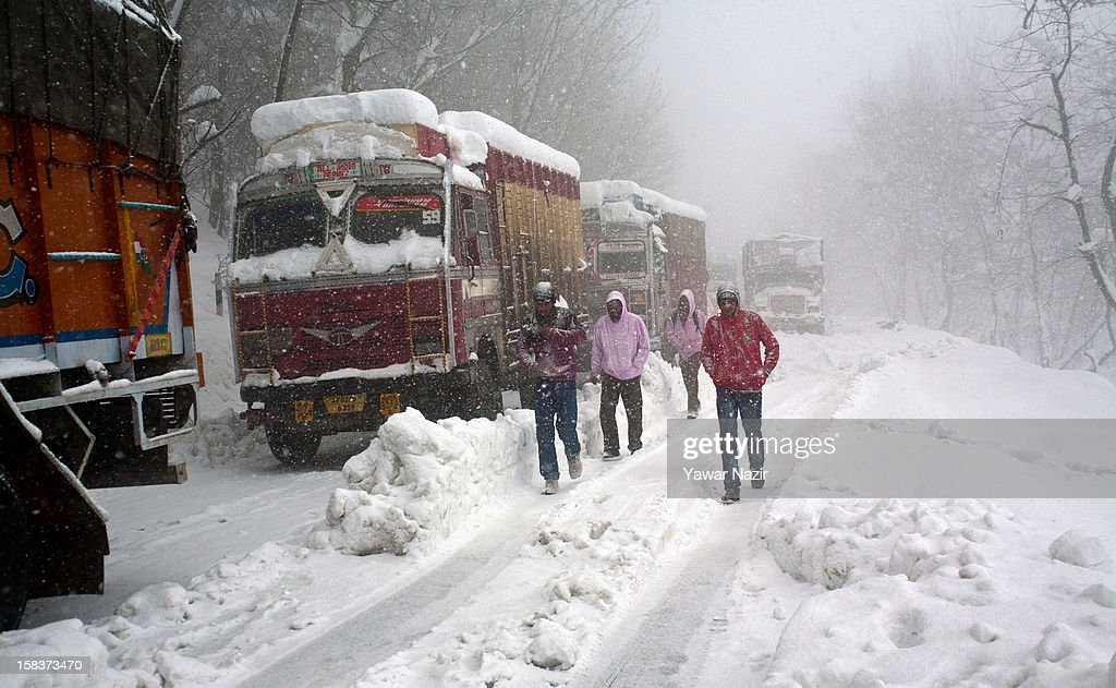 Stranded passengers walk with their luggage on Jammu Srinagar Highway amid heavy snowfall on December 14, 2012, in Banihal, 110 km (68 miles) south of Srinagar, the summer capital of Indian Administered Kashmir, India. Most parts of the Kashmir Valley, including Srinagar, received fresh snowfall, leading to closure of the 300 km (188 miles) Jammu-Srinagar Highway, the only road link between Kashmir and rest of India. Project Beacon authorities of the Border Roads Organisation, that maintains the highway, had already started efforts to clear the highway for traffic. The number of vehicles stranded on the highway was being ascertained.
