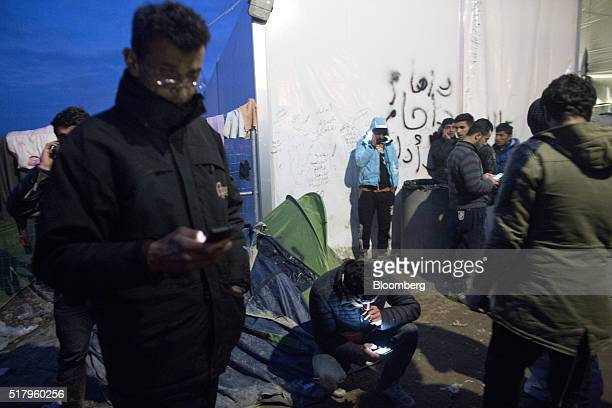 Stranded people take advantage of free wifi to use their mobile phones at a makeshift camp for refugees near the GreekMacedonian border in Idomeni...