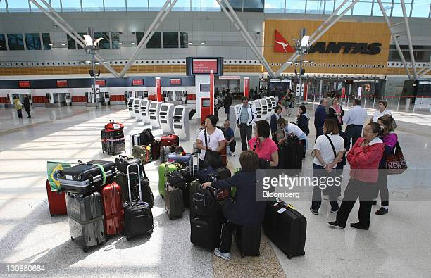 Stranded Qantas Airways Ltd travelers stand with their luggage in the domestic terminal at Sydney Airport in Sydney Australia on Monday Oct 31 2011...