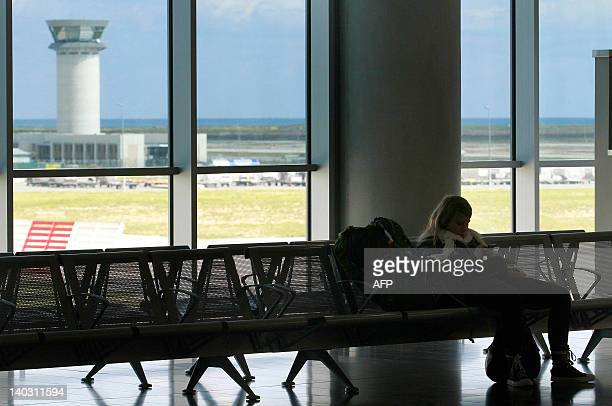 A stranded traveller sits inside Larnaca airport in the shadow of the air traffic control tower on March 2 as air traffic controllers on the...