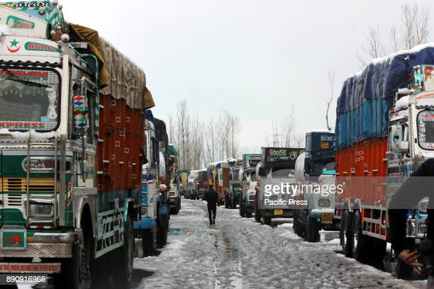Stranded truck drivers gossip next to their vehicles on closed SrinagarJammu highway on December 12 2017 in Lower Munda 85 km south of Srinagar the...