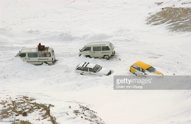 Stranded vehicles sit abandoned on a pass to the Salang Tunnel due to from heavy snow February 8 2002 about 80 miles north of Kabul Afghanistan...