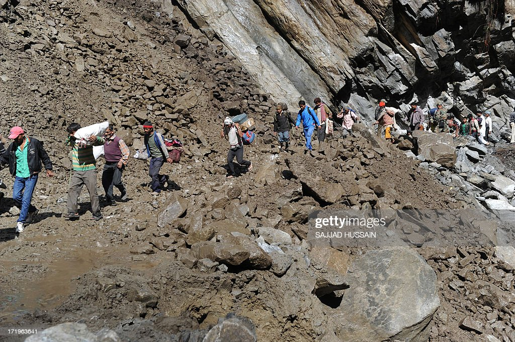 Stranded villagers make their way across a landslide caused by overnight rains as they make their way down the mountain in Govindghat following flash floods in northern Uttarakhand state on June 30, 2013. Some 3,000 tourists and pilgrims remain missing in India's flood-ravaged north two weeks after the tragedy, but it is unclear how many of those have been killed, a top state official said June 30.