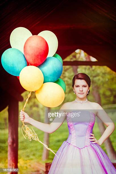 Strange girl in a colorful dress with balloons