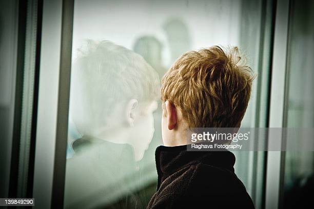 Stranger boy looking outside through glass