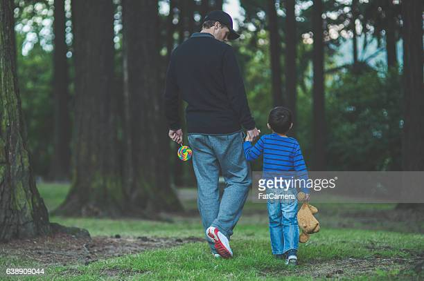 Stranger walking in a public park holding little boys hand