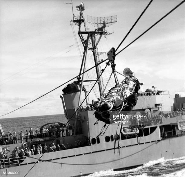 Strapped to a stretcher swinging over the ocean an American seaman taken ill aboard a United States destroyer escorting a convey to Korea is...
