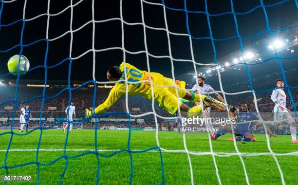 Strasbourg's Burkinabe defender Bakary Kone scores a goal next to Olympique de Marseille's French defender Adil Rami and Olympique de Marseille's...