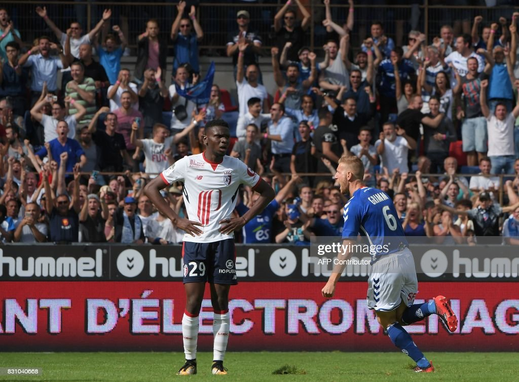 Strasbourg's French midfielder Jeremy Grimm (R) celebrates his goal as Lille's Malian midfielder Rominigue Kouame looks on during the French Ligue 1 football match between Strasbourg (RCSA) and Lille (LOSC) at The Meinau Stadium in Strasbourg, eastern France on August 13, 2017. /