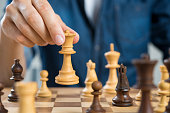 Close up of hand of man playing chess holding queen. Business man playing chess. Hand of casual businessman making a move with queen in chess. Business strategy and leadership concept.