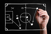 Hand drawing a football strategy plan drawn on a virtual screen