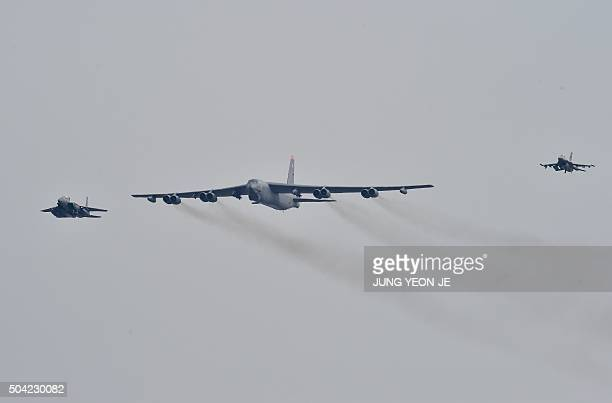 Stratofortress is escorted by a South Korean F15K fighter jet and a US F16 fighter jet as it flies over the Osan Air Base in Pyeongtaek south of...