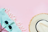 Straw beach sun-hat and sun glasses on punchy pink with space for text. Female outfit for beach. Summer concept.