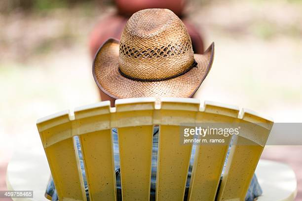Straw cowboy hat on a man in a yellow lawn chair