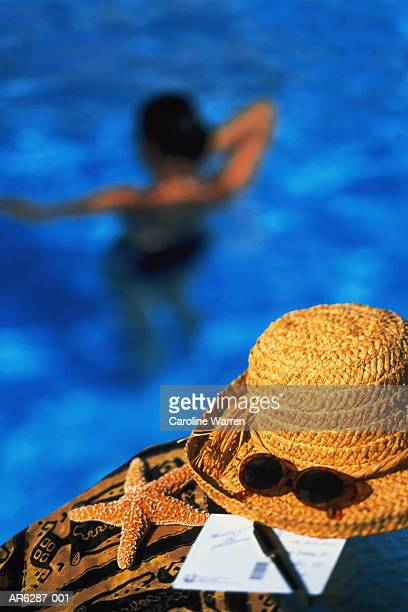 Straw hat and sunglasses, woman in pool in background (Composite)