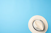 Straw hat on blue background. Top view