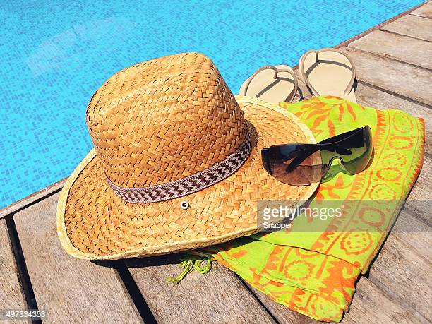 Straw hat, sunglasses, flip flops and sarong on wooden deck by swimming pool