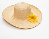 Woman's. woven, straw hat with yellow daisy isolated on white background.