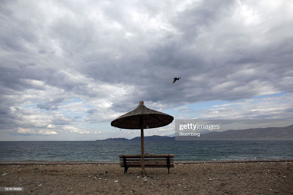 A straw parasol and bench stand on an empty tourist beach in Corinth, Greece, on Monday, Sept. 23, 2013. While the country's lenders are on firmer footing after getting capital from euro-area and International Monetary Fund bailout funds, they still need to reduce the non-performing loans that have tripled to 29 percent of the total in three years and threaten their new-found solvency. Photographer: Kostas Tsironis/Bloomberg via Getty Images