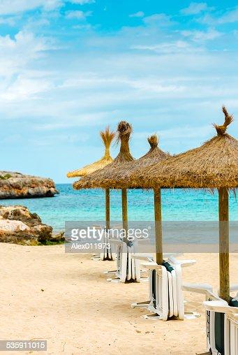Ombrelloni in paglia e lettini sulla spiaggia di sabbia : Foto stock