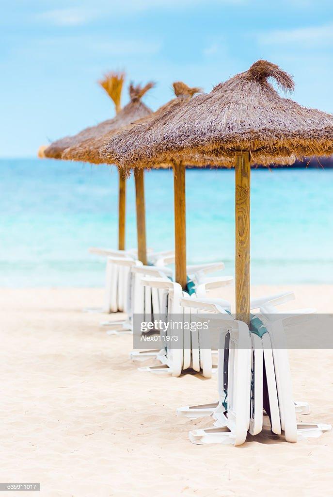 Palha parasols e camas na praia de areia : Foto de stock