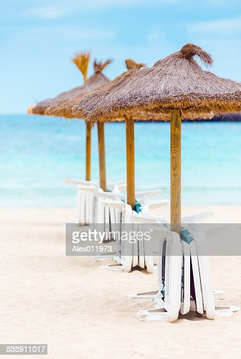 Straw parasols and beds on the sandy beach : Stock Photo