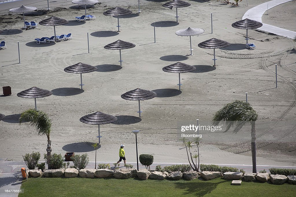 Straw parasols stand on the private beach at St Raphael resort hotel in Limassol, Cyprus, on Wednesday, March 27, 2013. Directly or indirectly, tourism makes up a quarter of Cyprus's economy with visitors from the two main tourism markets, Germany and U.K. Photographer: Simon Dawson/Bloomberg
