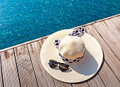 Straw sun hat and sunglasses on the terrace of swimming pool.