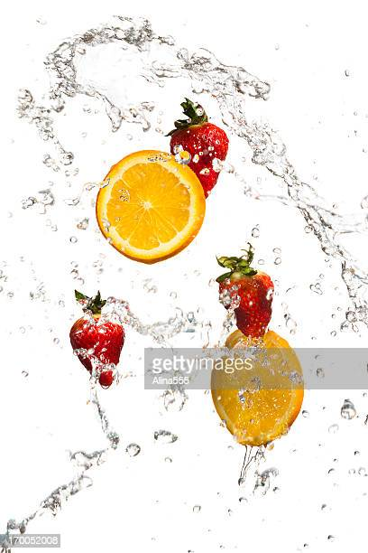 Strawberries and orange slices in a water splash