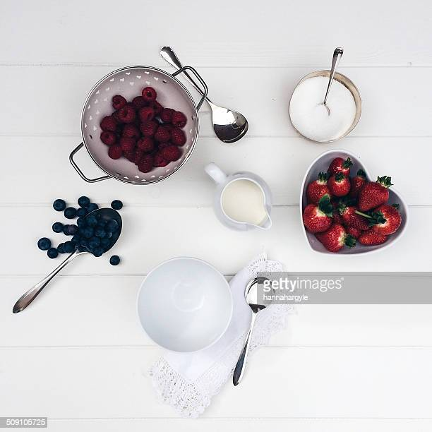 Strawberries, blueberries and raspberries with cream and sugar