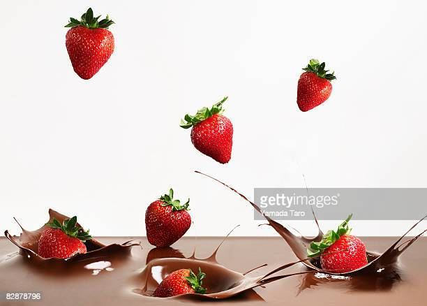 Strawberries dropped into chocolate