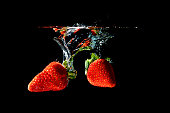 Strawberries falling into water on black background