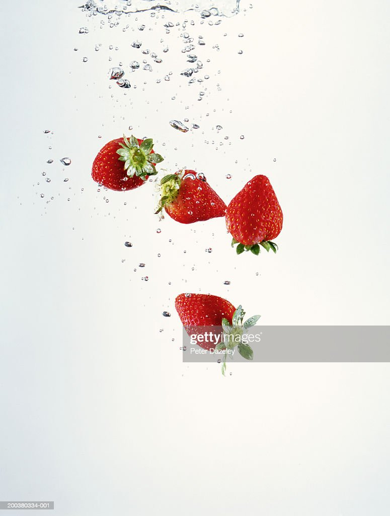 Strawberries falling through water (digital composite) : Stock Photo
