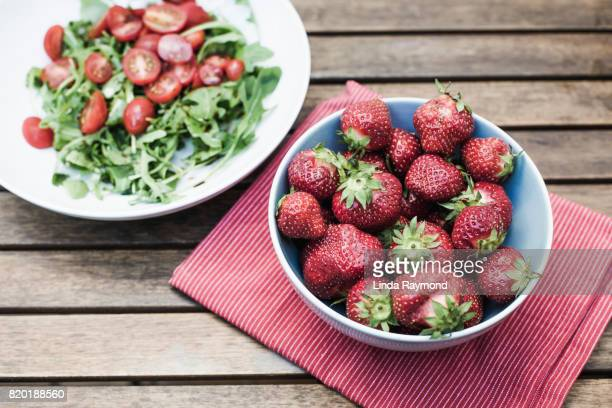 Strawberries in a bowl with aragula salad on wooden table